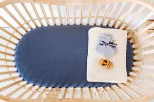 Rattan bassinet with navy blue sheet and cream knit blanket, blue booties and rattle