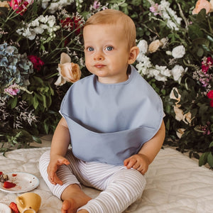 Toddler boy with a light blue bib, flowers in the background
