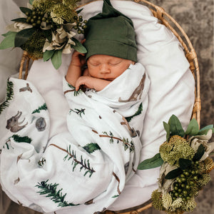 Baby wrapped in a swaddle in a basket wearing a green beanie