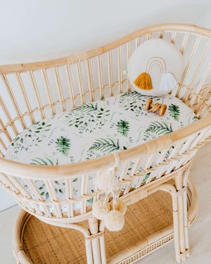 Rattan bassinet with white and green leaf sheet and pillow