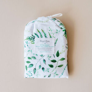 Photo of bassinet sheet in protective bag. Colour- white with green leavess