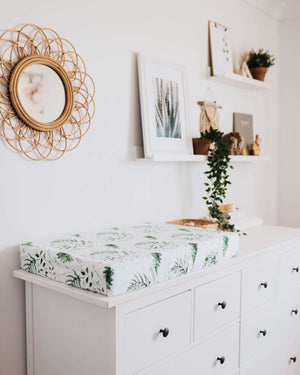 Chest of drawers with grean leaf and white change pad, photos and mirror in background on wall