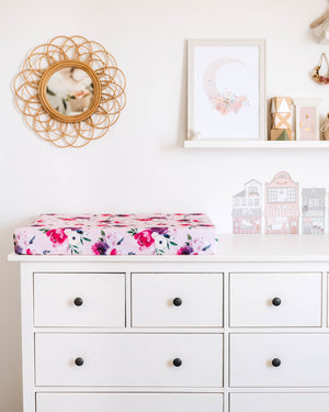 Photo of chest of drawers with pink and purple floral change pad cover, photos on the wall in the background and mirror on the wall