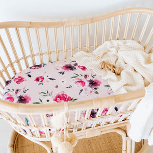 Rattan Bassinet with a floral pink and purple sheet and cream knit blanket