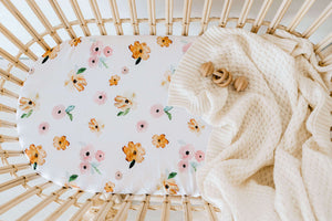 Rattan bassinet with a white sheet with pink and orange flower print and a cream knit blanket draped over the edge and wooden rattle