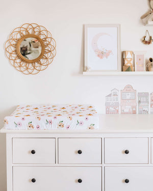 Chest of drawers with a white and pink and orange floral print change pad, photos and mirror on the wall in the background