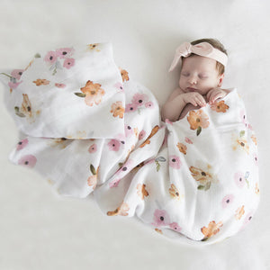 Baby wrapped in a white and pink floral print wrap wearing a bow
