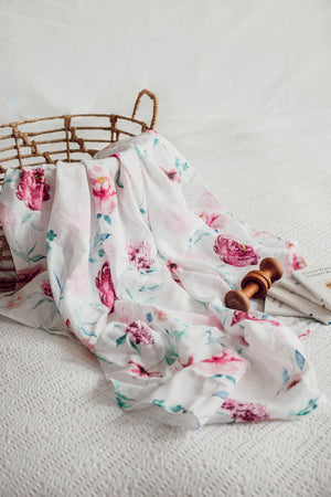 White, pink and green swaddle draped over basket