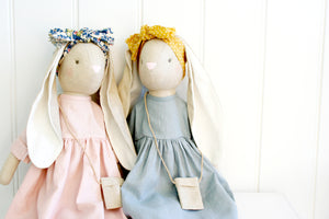 Alimrose Sofia Bunny in blue dress and mustard headband sitting with bunny in pink dress and floral headband