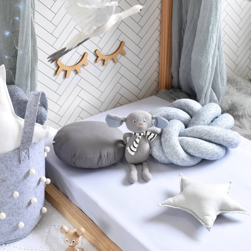 Toddler bed with a stone coloured cot sheet, 3 pillows and a toy elephant on it. Grey basket next to the bed