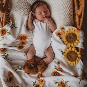 Newborn baby in basket laying on a sunflower print wrap and bow headband on head