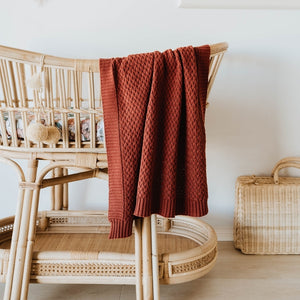 Rust coloured knot blanket draped over ratton bassinet