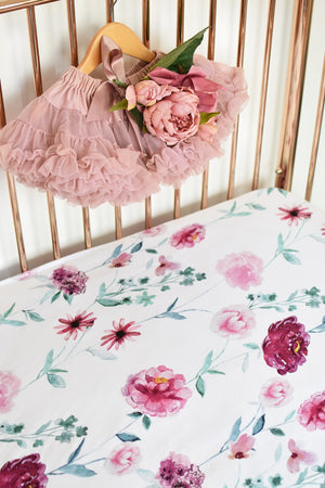 white and pink floral fitted cot sheet on gold cot