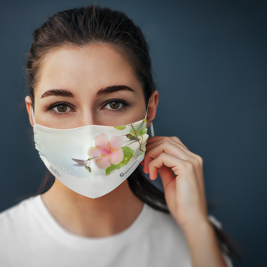Woman wearing a hummingbird and hibiscus face mask by Glen Loates