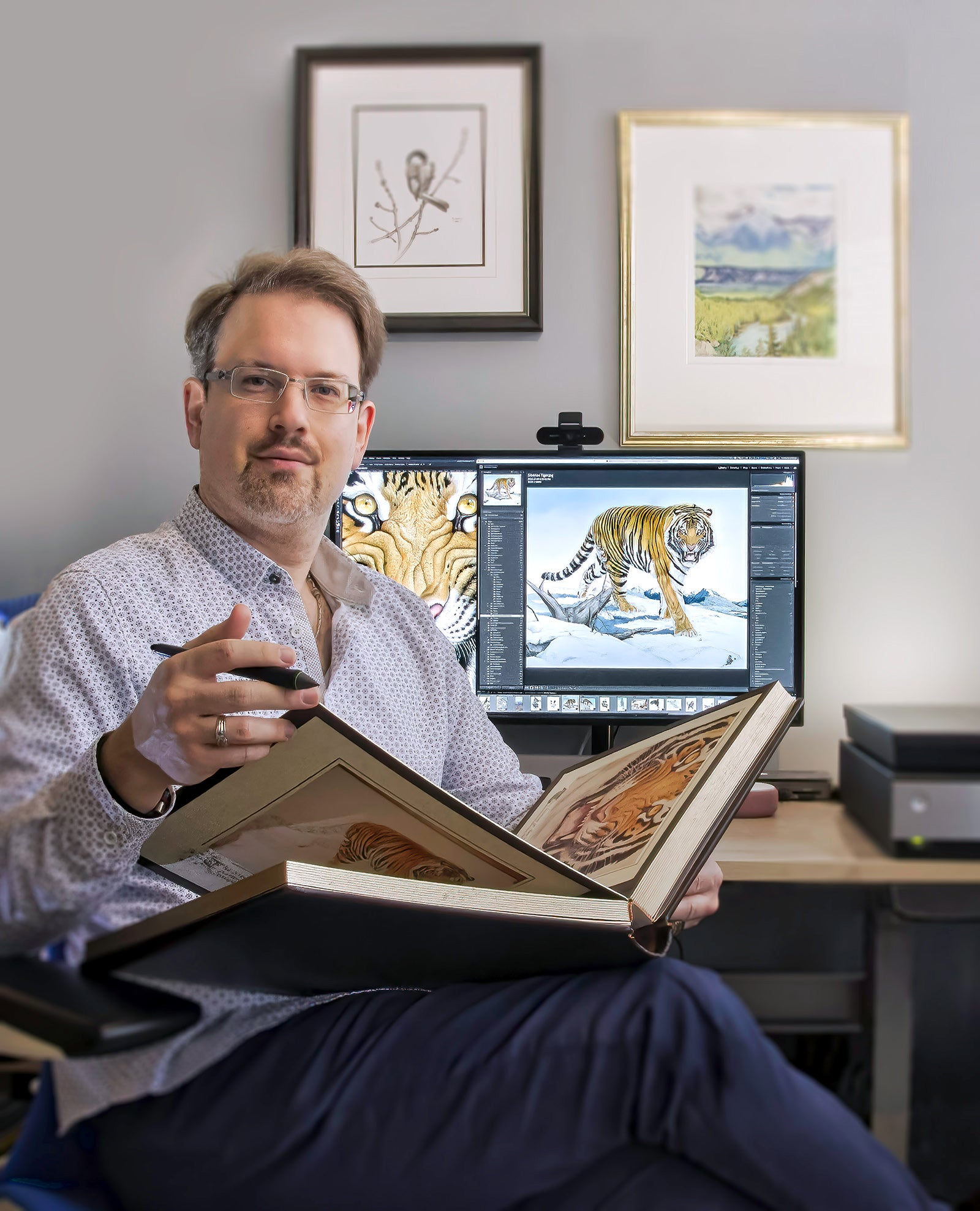 Michael Loates sitting at his desk working on the Glen Loates Siberian Tiger Book.