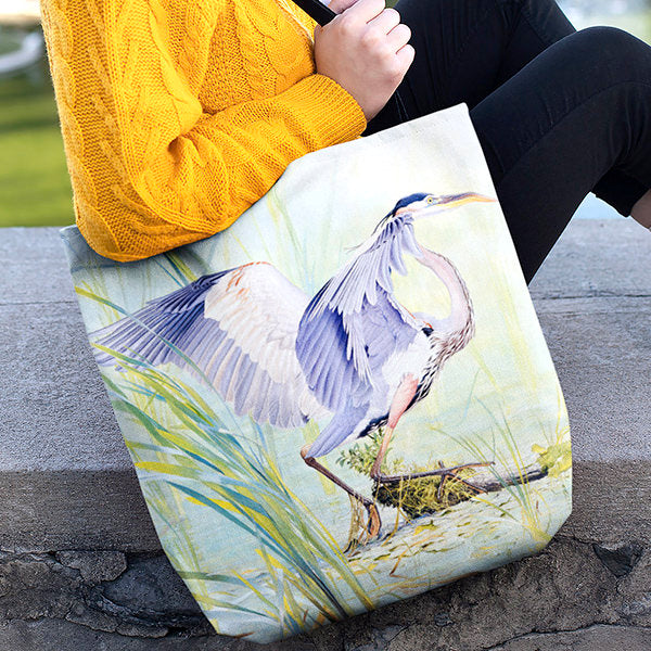 Woman sitting and holding a Great Blue Heron tote bag by Glen Loates