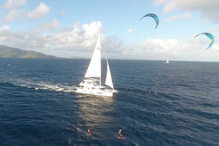 kiteboarding sunset session alongside catamaran