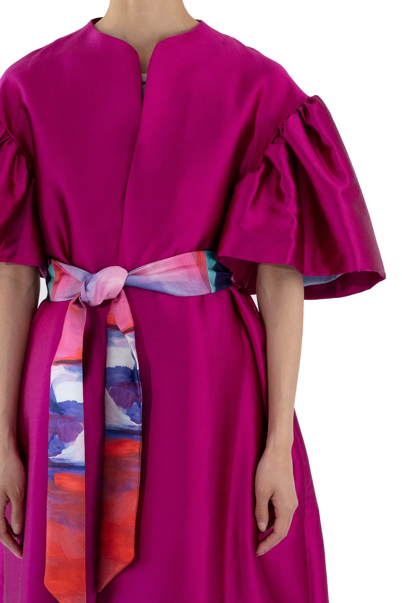 Close up of fuchsia opera coat with floral printed belt