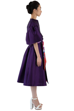 Side view of women's belted purple opera coat