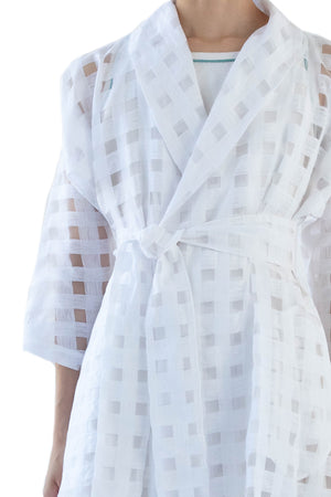 Close up of belted semi sheer white wrap dress