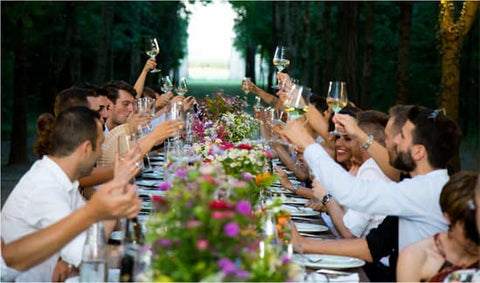 Wedding Guests all sitting at the table raising their glasses to a toast