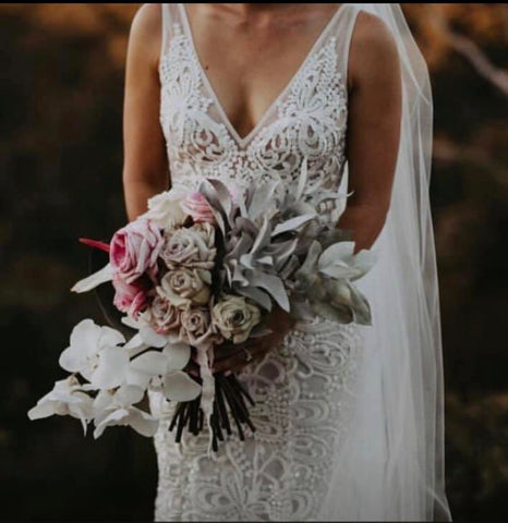 Showing Bride from neck down to knees and holding bouquet of flowers