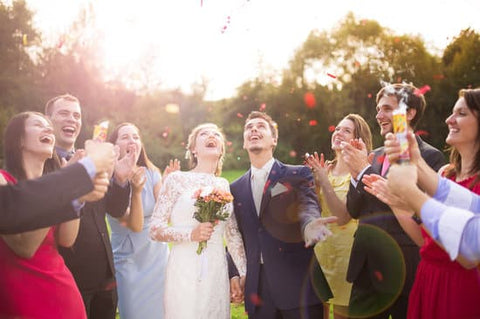 Bride and groom surrounded by guests looking up as rose petals fall on them