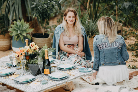 Bride to be at a picnic with her back to you with the writing BRIDE on the back of her vintage levi denim jacket