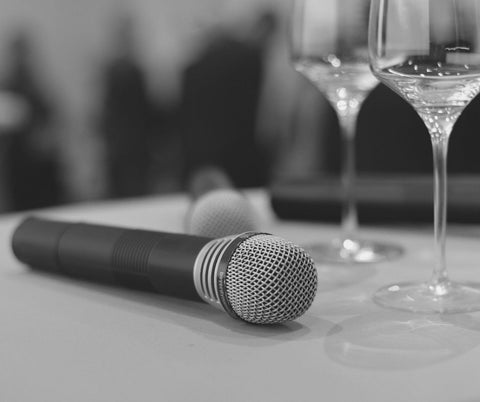 Microphone laying on table with two glasses of wine sat behind it