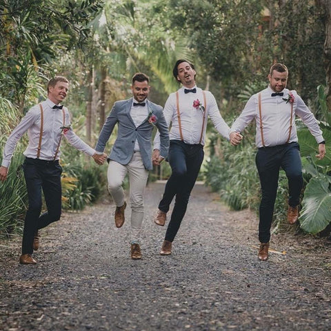 Groom skipping holding hands with his 3 groomsmen on a paved road