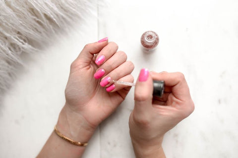 Lady painting her nails bright pink