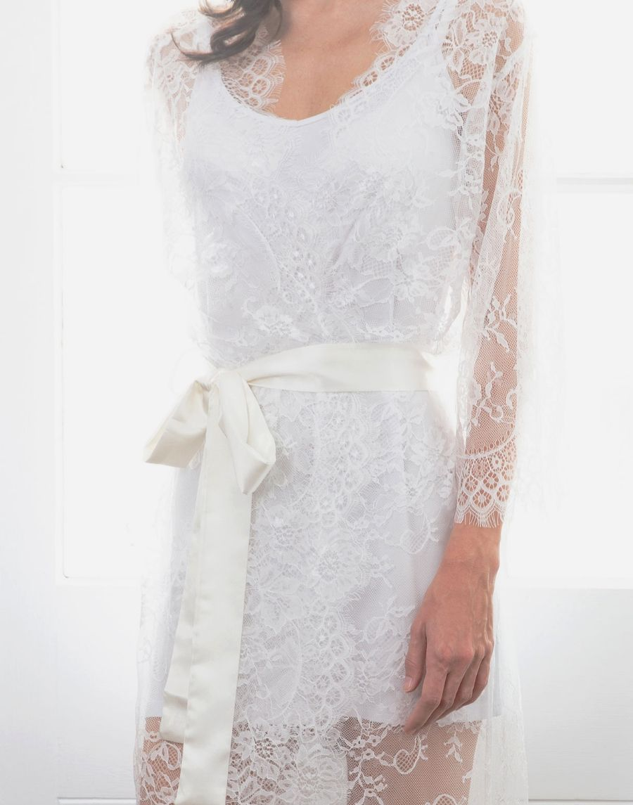 An image of the Alma full lace maxi bridal robe. The lace robe is worn with a simple white slip underneath. The lace is intricate, delicate and very elegant. The robe is fastened with a satin ribbon belt sash, above the hips.
