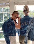 Load image into Gallery viewer, Bride and Bridesmaid standing together with their backs to you and both wearing vintage denim jackets. The bridesmaids says TRIBE in sparkling large letters on the back