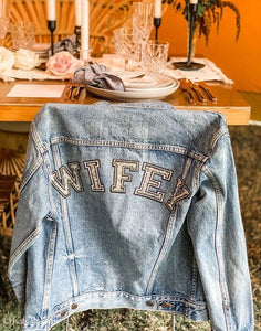 Vintage denim jacket on the back of a chair with WIFEY writing on the back of the jacket