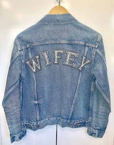 Vintage denim jacket hanging up on a coat hanger with the back facing you with WIFEY written on the top of the jacket in sparkly writing