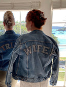 Load image into Gallery viewer, Vintage denim jacket worn by a bride with her back facing you with WIFEY written on the top of the jacket in sparkly writing