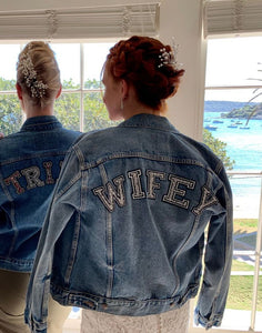 Vintage denim jacket worn by a bride with her back facing you with WIFEY written on the top of the jacket in sparkly writing