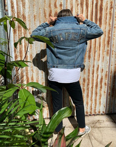 Vintage denim jacket worn by a women in casual pants and sneakers with her back facing you with WIFEY written on the top of the jacket in sparkly writing