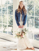 Load image into Gallery viewer, Smiling Bride standing wearing wedding dress and vintage denim jacket holding a bouquet of flowers