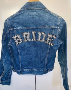 Blue denim jacket on coat hanger with the back of it facing you with BRIDE written on the top of the back