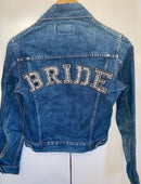 Load image into Gallery viewer, Blue denim jacket on coat hanger with the back of it facing you with BRIDE written on the top of the back