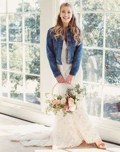 Bride facing you in wedding dress and denim jacket smiling holding onto a flower arrangment