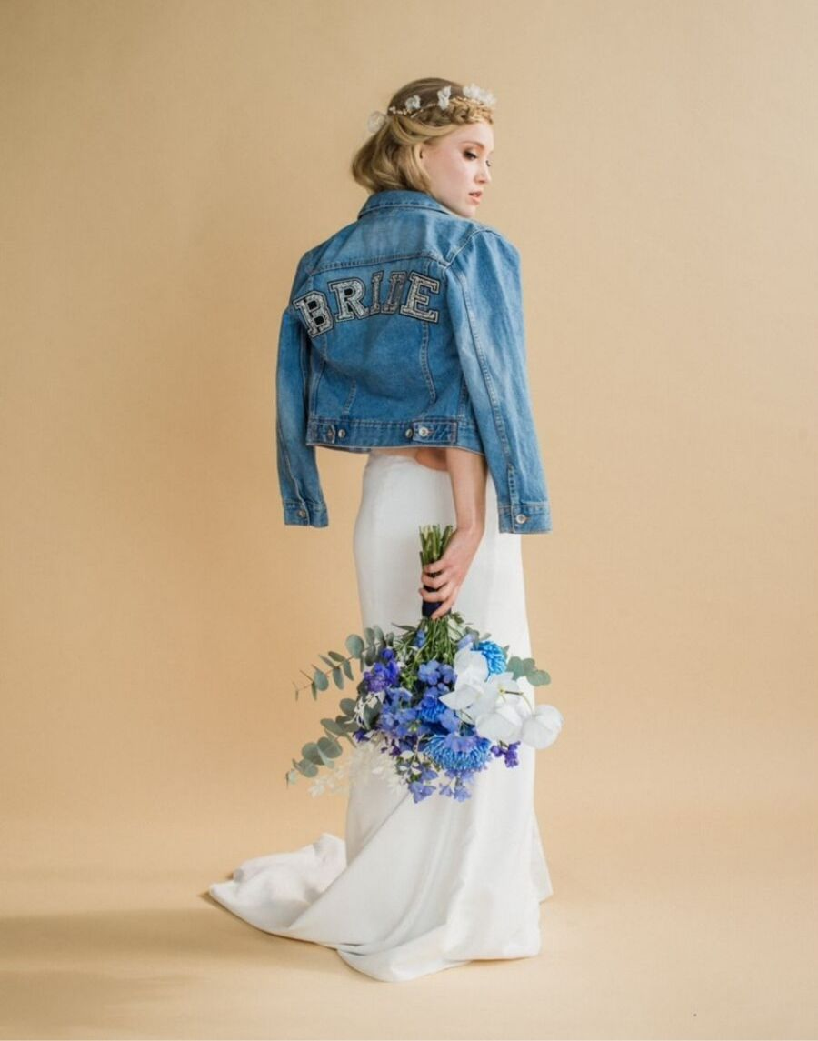 Bride standing with her back to you with head tilted to the right looking to the side. Bouquet of flowers pointing at the ground in her hand and blue denim jacket over her dress saying BRIDE