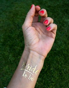 A different closeup image of the Gold Bride To Be tattoo on a wrist. Bride to be is written in funky cursive font with a casual underline under Bride. The dainty design looks lovely on the wrist & the gold is shimmering in the sunlight.