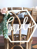 Load image into Gallery viewer, A close up image of the Bride sign on the back of a wicker style chair which is set with greenery & subtle pink roses.