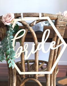 A close up image of the Bride sign on the back of a wicker style chair which is set with greenery & subtle pink roses.