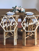 Load image into Gallery viewer, An wide angle image of the BRIDE and GROOM wooden chair signs. Both signs are placed on the back of matching wicker style chairs on a table which is beautifully set with greenery and subtle pink roses.