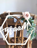 Load image into Gallery viewer, A close up image of the Groom sign on the back of a wicker style chair which is set with greenery & subtle pink roses.