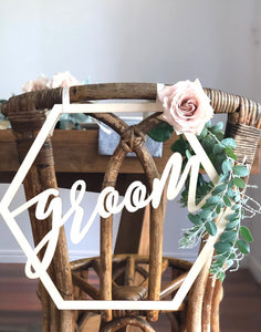 A close up image of the Groom sign on the back of a wicker style chair which is set with greenery & subtle pink roses.