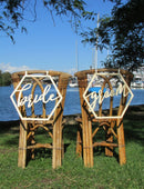 Load image into Gallery viewer, A wide angle image of the BRIDE and GROOM wooden chair signs. Both signs are placed on the back of matching wicker style chairs on the grass overlooking the river.